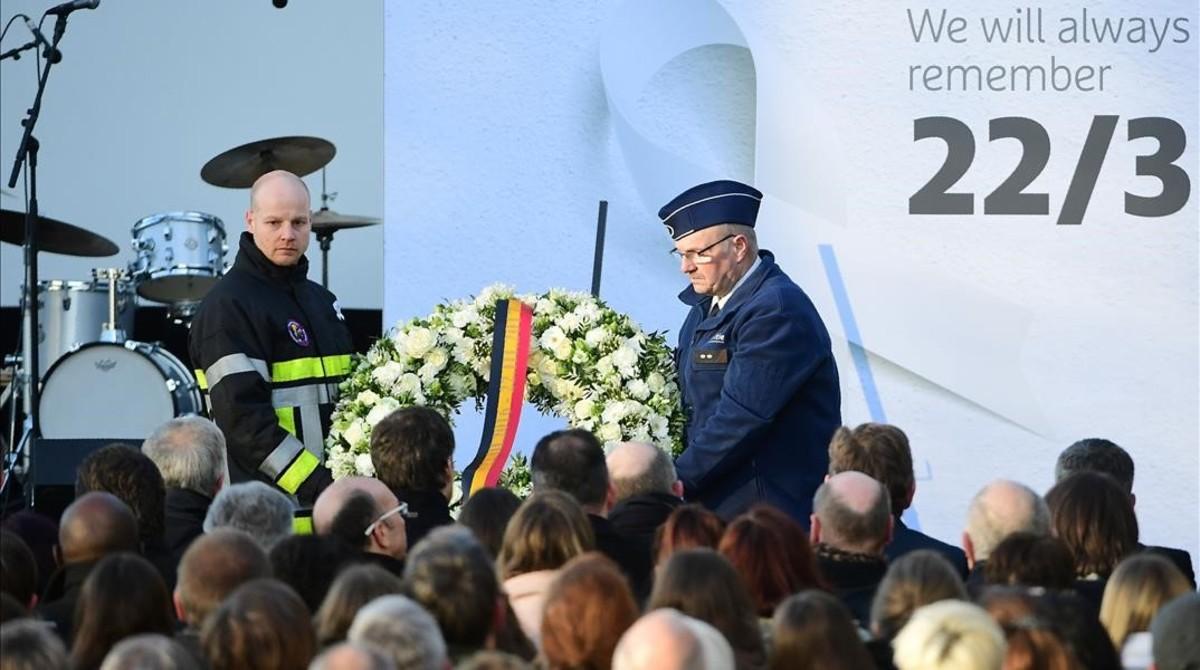 Un bombero y un agente de seguridad colocan un corona de flores en el aeropuerto de Zaventem, durante el homenaje a las víctimas de los ataques yihadistas, en Bruselas, el 22 de marzo.