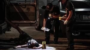 Un cadáver junto a un vehículo acribilladoen Manila.