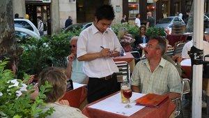 Un camarero toma nota de las peticiones de uncliente.