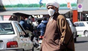 Un clérigo iraní trata de protegerse con una mascarilla de la propagación del coronavirus.