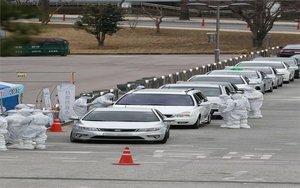 Personal médico revisa autos por coronavirus en Corea del Sur.