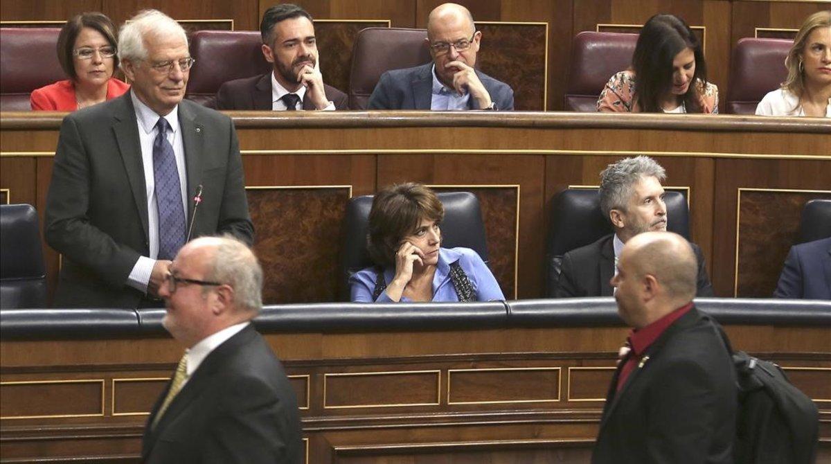 El diputado Jordi Salvador (ERC), con la camisa roja, pasa por delante del ministro Josep Borrell, que le acusó de haberle escupido.