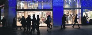 Siluetas frente a la tienda de Urban Outfitters en el Triangle de la plaza de Catalunya en una jornada de compras.