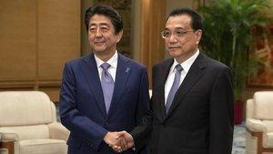 El primer ministro chino, Li Keqiang, a la derecha, y el primer ministro japonés, Shinzo Abe, se dan la mano durante su reunión en Pekín este jueves 25 de octubre.
