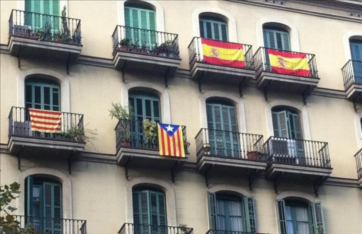 Fachada de un edificio de Barcelona con banderas española, una 'senyera' y una 'estelada'.