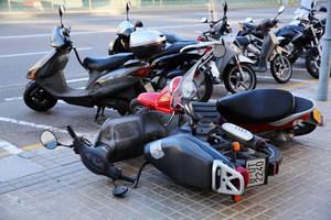 El fort vent tira a terra diverses motos al passeig de Taulat de Barcelona, aquest dimarts.