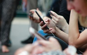Un grupo de personas consulta sus teléfonos móviles.