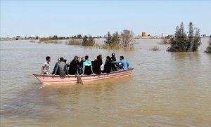 Iranís de la provincia de Golestan, anegada por las lluvias, en una barcaza a finales de marzo.