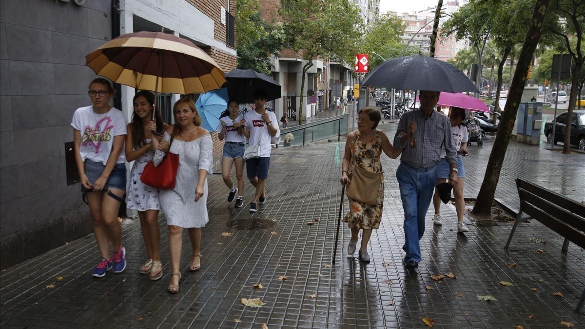 Transeúntes con paraguas en la Ronda del Guinardó, en una imagen de archivo.