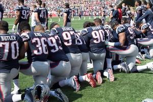 Los jugadores de New England Patriots protestan arrodillados durante el himno.