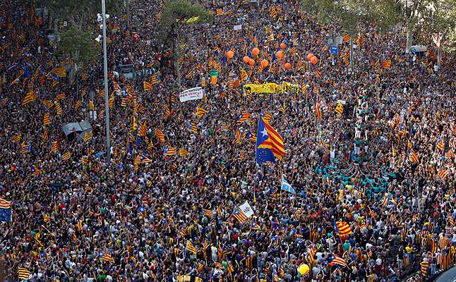 A la espera del inicio de la manifestación, cientos de miles de personas observan una torre de 'castellers' en Paseo de Gracia con Gran Vía
