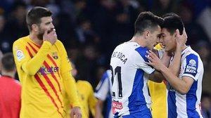 Marc Roca, a la derecha, felicita a Wu Lei por su gol, ante la desolación de Gerard Piqué.