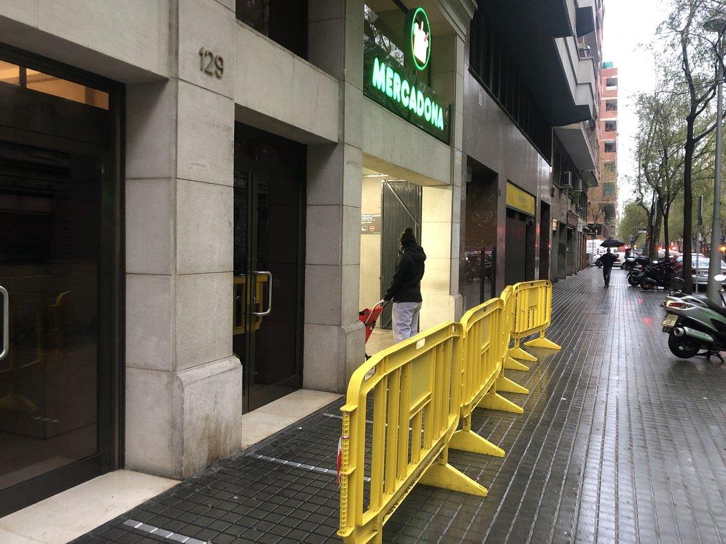La entrada de un Mercadona con vallas y marcas en el suelo de separación de clientes, por si es necesario hacer cola en la calle.