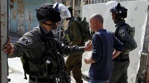 Soldados israelies arrestan a un joven palestino durante una protesta en la ciudad cisjordana de Hebron ayer lunes17 de abril.