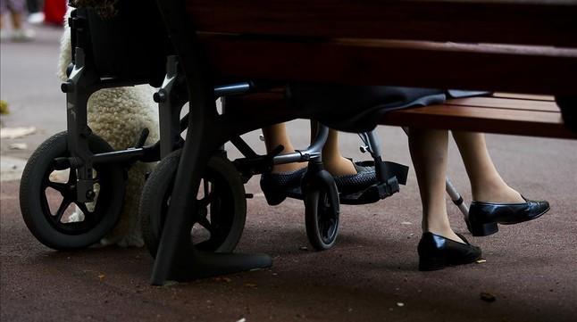 Personas mayores descansan en un banco.