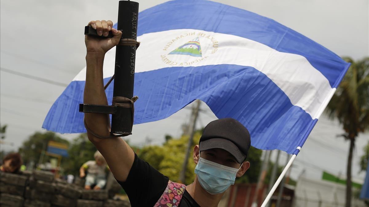 Un joven manifestante alza su arma artesanal y la bandera nacional en Managua.
