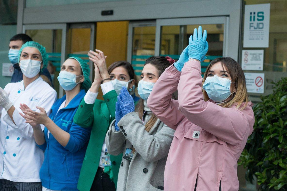 Enfermeras de la Fundación Jiménez Díaz hacen entrega a la Policía Local de Madrid unas mascarillas fabricadas por ellas mismas, durante el homenaje diario a sanitarios que se celebra en el puerta de la Fundación en Madrid, a 31 de marzo de 2020.