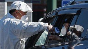 El trabajador de un cementerio de Pekín toma la temperatura a un conductor antes de que acceda al recinto.
