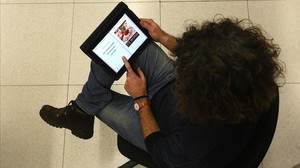 Una lectora, consultandoun libro de recetas en una tablet.