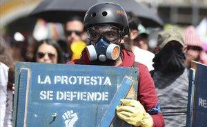 Una manifestante sostiene un cartel de protesta en una marcha en Bogotá contra el Gobierno de Duque.