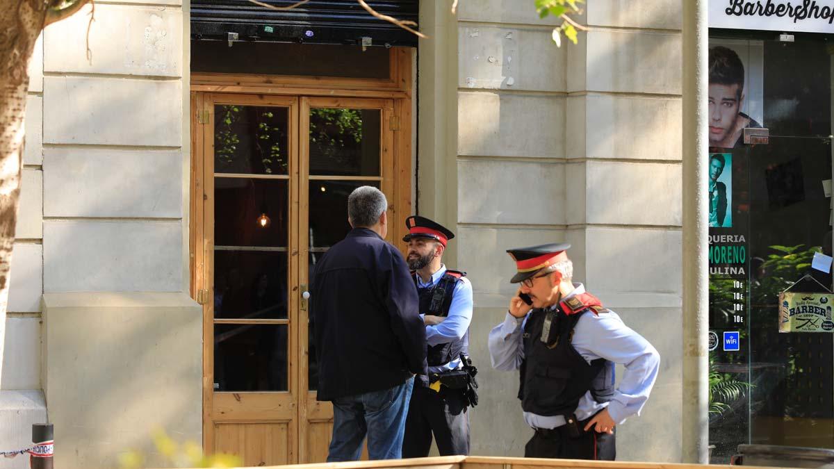Vecinos depositan flores y velas frente al bar del Eixample de Barcelona donde fue asesinada una menor. En la foto, Mossos frente al local.