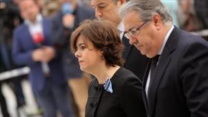 La vicepresidenta del Gobierno, Soraya Sáenz de Santamaría y el ministro del Interior, acudiendo al funeral.