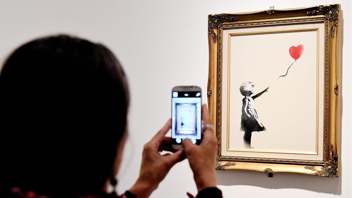Una mujer toma una foto del lienzoLa chica con globo.