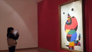 Una visitante observa 'Mujer, pájaro, estrella (Homenaje a Pablo Picasso), un óleo de 1973.