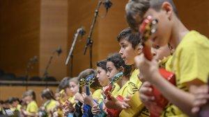 Niños tocan el ukeleleen el estreno de Gall de foc, en el Auditori.