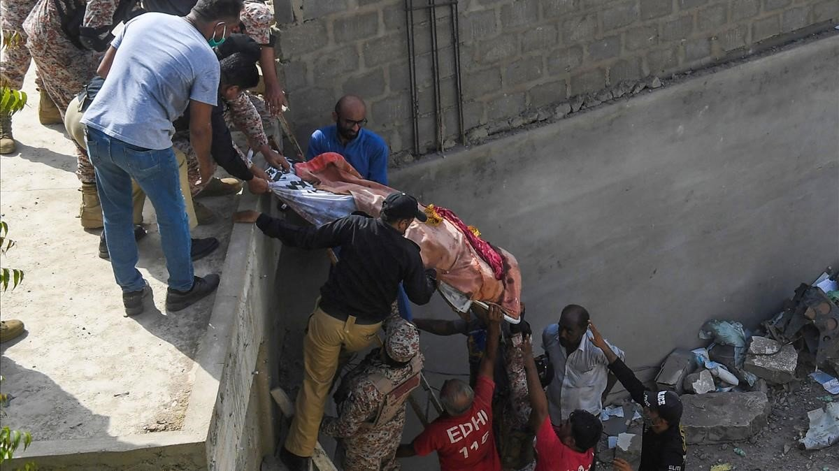 Los equipos de rescate trasladan a un fallecido.