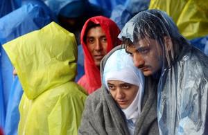 Refugiados bajo la lluvia esperando entrar en territorio esloveno.
