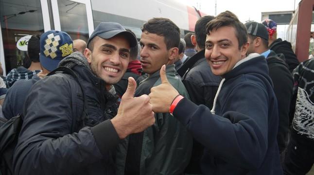 Unos refugiados se hacen un selfi antes de subir al tren con destino a Austria.