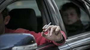 Un conductor saca el brazo por la ventanilla de su coche, en el que viaja un niño, mientras sostiene un cigarillo.