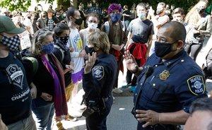 Agentes de policía de Seattle, rodeados por manifestantes en una marcha en la ciudad.