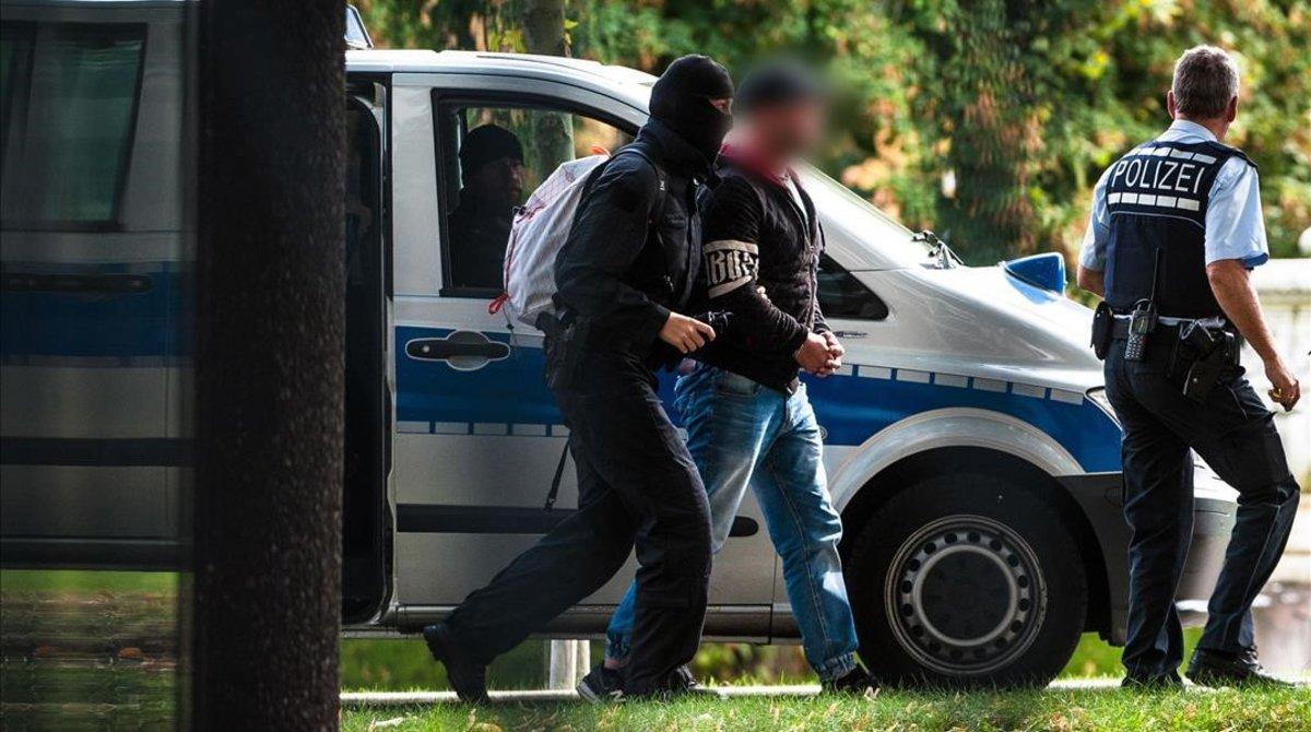 Agentes de policia trasladan a uno de los detenidos en la operación contra la ultraderecha en Alemania.