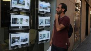 Un joven consulta las ofertas de piso en una agencia inmobiliaria de Barcelona.