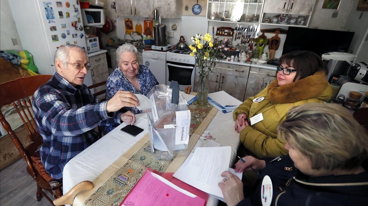Ancianos rusos votan en su casa, en Dedukino, gracias a una mesa electoral móvil.