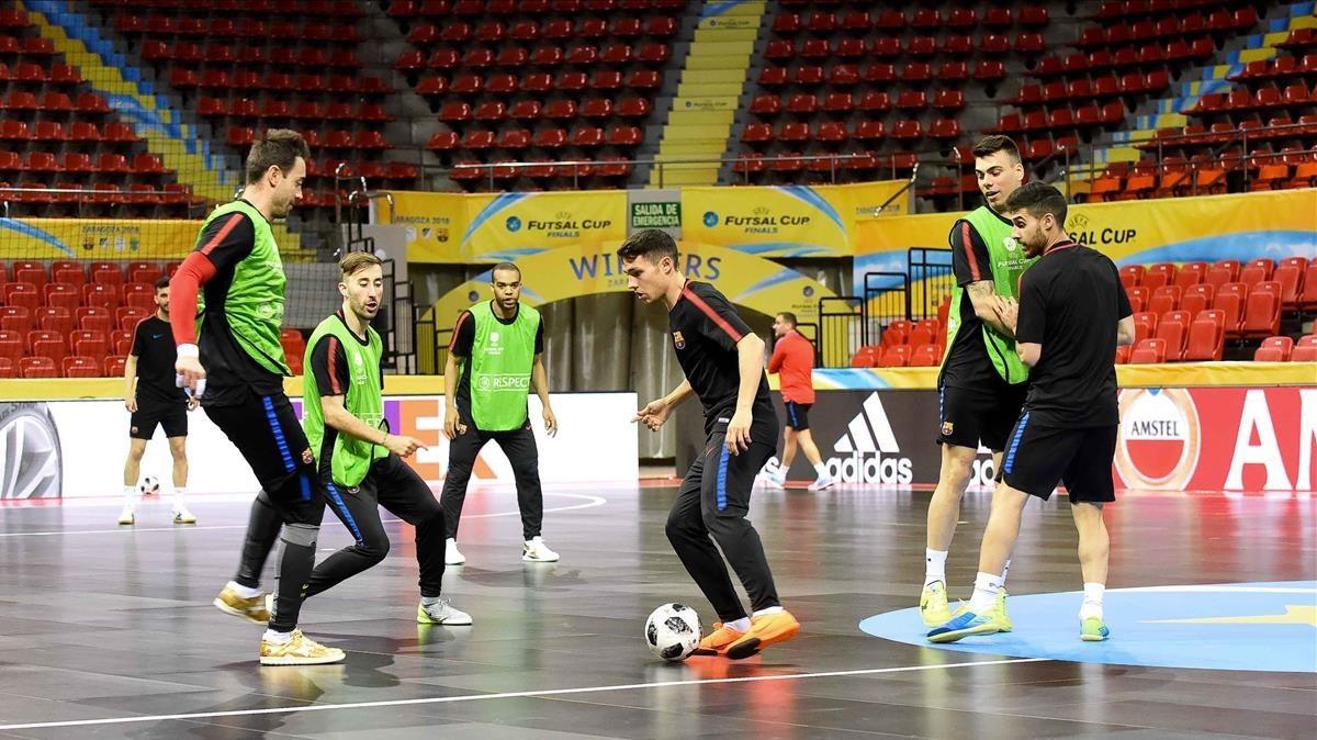 Roger Serrano, con el balón, rodeado de compañeros durante un entreno en el Pabellón Príncipe Felipe de Zaragoza.