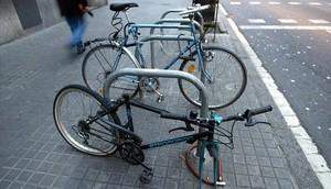 Cuadro de una bicicleta con unaruedarobadaen una estacionamiento en U en una calle de Barcelona.