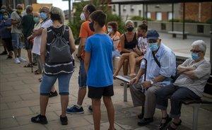 Gente con mascarilla espera su turno para realizarse una prueba PCR en Santa Coloma de Gramenet.