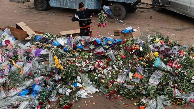 Trabajadores de un invernadero de San Petersburgo destruyen flores que se están marchitando porque no se pueden vender.
