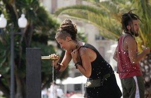 Una joven se refresca en una fuente del paseo de les Palmeres, en Tarragona.