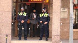 Dos agentes custodian el portal del edificio donde ha aparecido muerta una mujer.