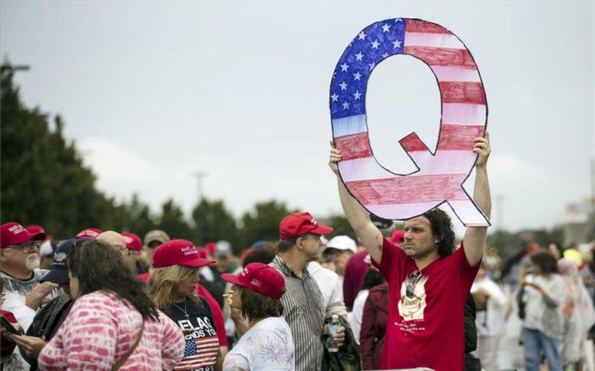 Una persona sostiene el símbolo del movimientoQAnon.