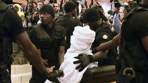 Habré, completamente tapado con una vestimenta blanca, rodeado de policías en el tribunal, en Dakar, este lunes.