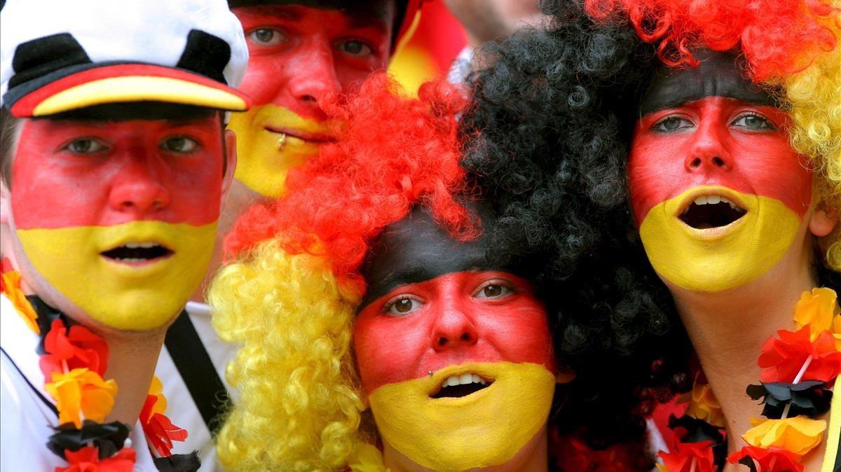 Aficionados alemanes animan a su seleccion en un partido de fútbol.