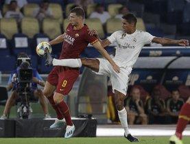 El madridista Varane (d) intenta cortar un balón ante Dzeko.