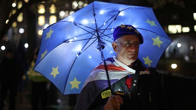 Un partidario pro-UE se refugia bajo una sombrilla con labandera europea junto al Parlamento en Westminster