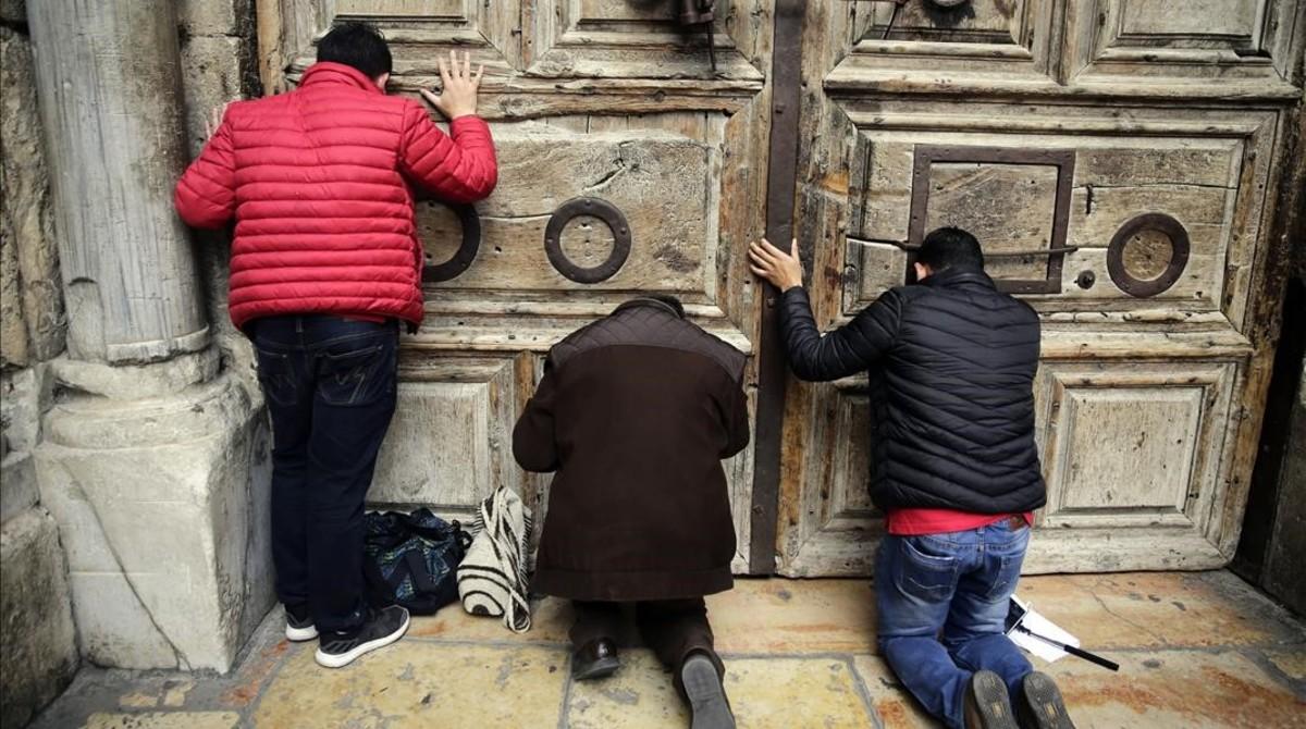 Peregrinos rezan en al puerta del Santo Sepulcro, cerrado.