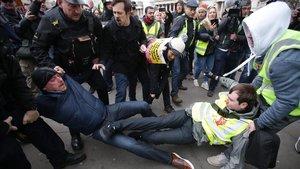 La policía británica y otros manifestantesseparan a un partidario y un detractor del brexit en una marcha en Londres.